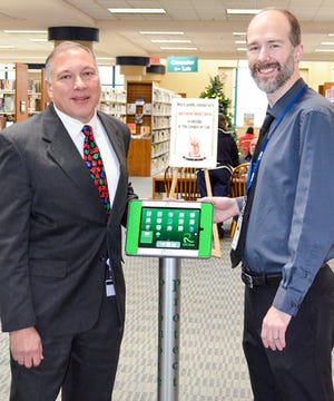 Health Commissioner Martin Tremmel and Mansfield/Richland County Libraries Director Chris May stand next to the new health kiosk inside the library's main branch.