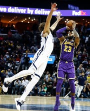 Los Angles Lakers  guard LeBron James (right) puts up a 3-pointer against Memphis Grizzlies defender Joakim Noah (left) during action at the FedExForum in Memphis, Tenn., Monday, February 25, 2019.