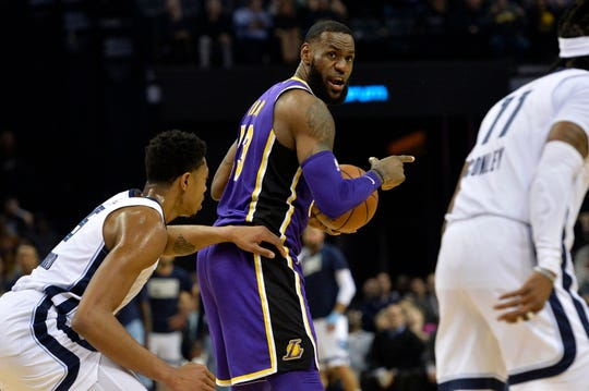 Los Angeles Lakers forward LeBron James, center calls to teammates as he controls the ball against Memphis Grizzlies forward Bruno Caboclo, left, in the first half of an NBA basketball game Monday, Feb. 25, 2019, in Memphis, Tenn. (AP Photo/Brandon Dill)