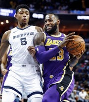 Los Angles Lakers  guard LeBron James (right) drives the lane against Memphis Grizzlies defender Bruno Caboclo (left) during action at the FedExForum in Memphis, Tenn., Monday, February 25, 2019.