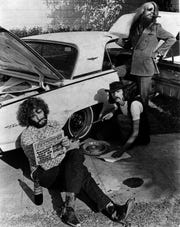 Leon Russell, at right, Don Nix, changing tire, and Denny Cordell, Russell's partner in Shelter Records: A gag photo that shows what else is required of Nix as he signs a contract with the Shelter label.