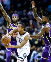 Memphis Grizzlies guard Avery Bradley (middle) makes a pass while guarded by Los Angles Lakers defenders Brandon Ingram (left) and Reggie Bullock (right) during action at the FedExForum in Memphis, Tenn., Monday, February 25, 2019.