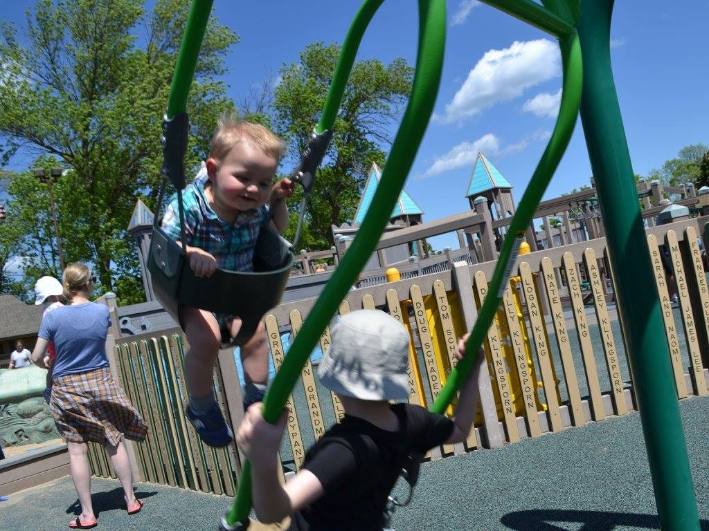 Children enjoy the swings at Possibility Playground in Port Washington.