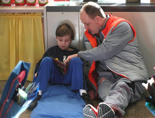 Carroll University men's head basketball coach Paul Combs helps Nate Siepe-Pick, a third-grader at Whittier Elementary School in Waukesha, with his reading.
