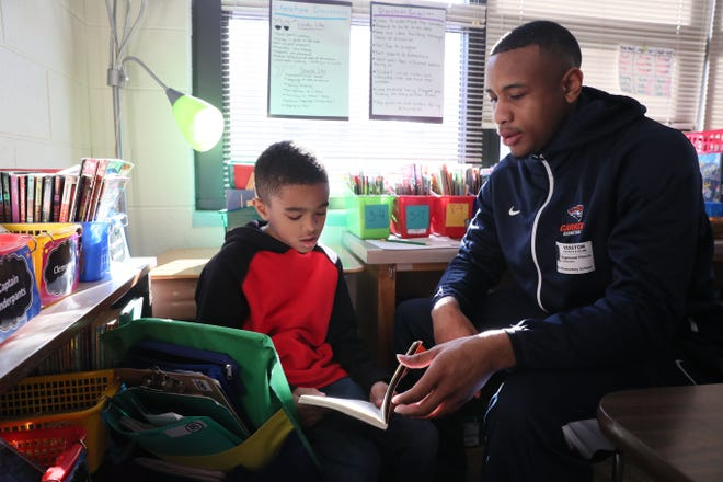 Carroll University basketball player Ray Pierce helps Za'yre Handy, a third-grader at Whittier Elementary School in Waukesha, with his reading earlier this month.