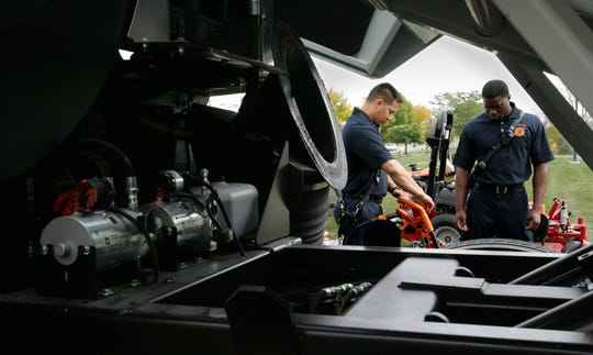 Tai Rondeau (left) and Justin Young of the Greenfield Fire Department check out some power equipment in this 2014 file photo. Greenfield and Franklin have agreed to fund a study that would examine ways fire departments from both communities could share services.