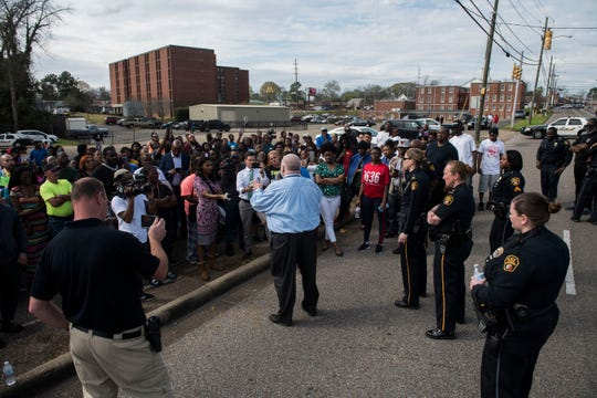 Officials talk to concerned parents as emergency crews investigate a shooting at Lee High School in Montgomery, Ala., on Tuesday, Feb. 26, 2019.
