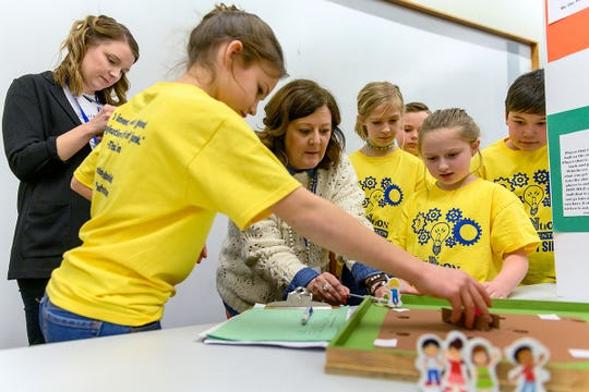 MTSU Invention Convention judges Katie Schrodt, left, a Department of Elementary and Special Education professor, and Middle Tennessee Christian School Principal Melanie Maxwell, center, play with the 'Kickball King' board game invented by Erma Siegel Elementary fourth-graders Aurora Nelson-Keener, Lillian Bunney and Claire Couey as some of their classmates watch Feb. 21 in the MTSU Student Union Ballroom. They were voted Judges Favorite in the Fourth Grade Games category.