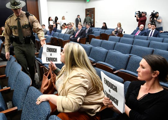 A state Trooper escorts protestors out of the House Education Administration subcommittee for holding signs where Representative David Byrd is the Chairman. 