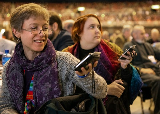 Sara Isbell joins other delegates at the 2019 Special Session of the General Conference of The United Methodist Church in St. Louis, Mo., Tuesday, Feb. 26, 2019. America's second-largest Protestant denomination faces a likely fracture as delegates at the crucial meeting move to strengthen bans on same-sex marriage and ordination of LGBT clergy. (AP Photo/Sid Hastings)