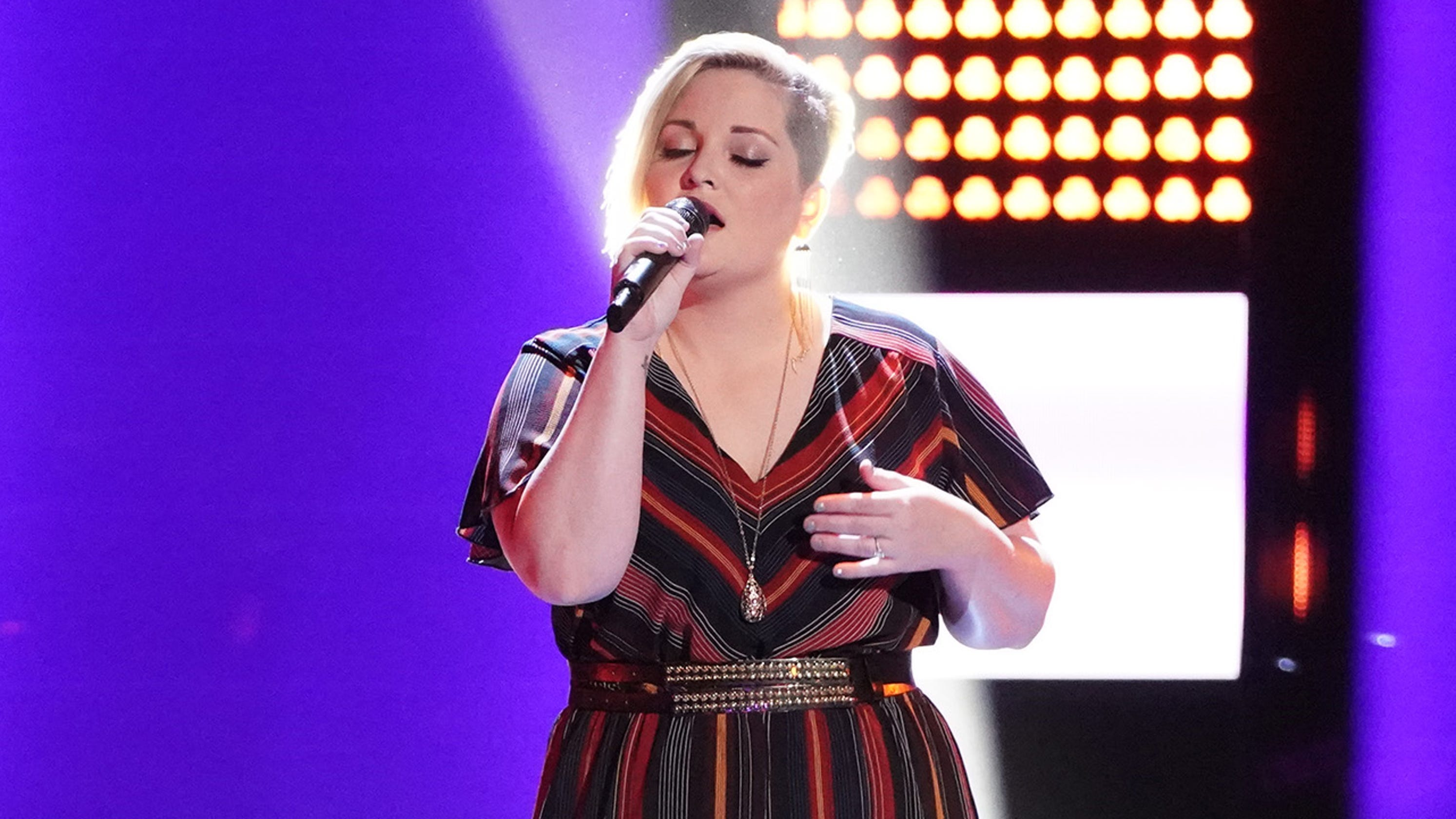 Rizzi Myers holding a mic while performing on the stage of The Voice