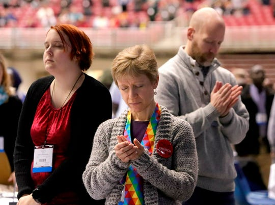 Standing in prayer are delegates Kimberly Woods, from left, of Industry, Ill., Sara Isbell, of Bloomington, Ill., and Andy Adams, of Troy, Ill., at the United Methodist Church General Conference Day of Prayer, Saturday, Feb. 23, 2019, at The Dome at America's Center in St. Louis. (Hillary Levin/St. Louis Post-Dispatch via AP)