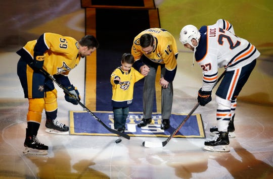 Former Nashville Predators center and captain Mike Fisher watches as his son, Isaiah, drops a ceremonial puck for Predators defenseman Roman Josi (59), of Switzerland, and Edmonton Oilers left wing Milan Lucic (27) as Mike Fisher is honored before an NHL hockey game Monday, Feb. 25, 2019, in Nashville, Tenn.