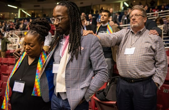 Adama Brown-Hathasway, left, The Rev. Dr. Jay Williams, both from Boston, and Ric Holladay of Kentucky join in prayer during the 2019 Special Session of the General Conference of The United Methodist Church in St. Louis, Mo., Tuesday, Feb. 26, 2019. America's second-largest Protestant denomination faces a likely fracture as delegates at the crucial meeting move to strengthen bans on same-sex marriage and ordination of LGBT clergy. (AP Photo/Sid Hastings)