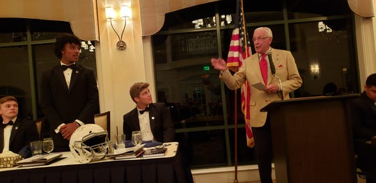 Pete Dawkins (right), the 1958 Heisman Trophy winner and former brigadier general in the army, highlights Golden Gate's Jordan Williams (standing) during his speech at the National Football Foundation Collier County chapter's banquet on Monday, Feb. 25, 2019.