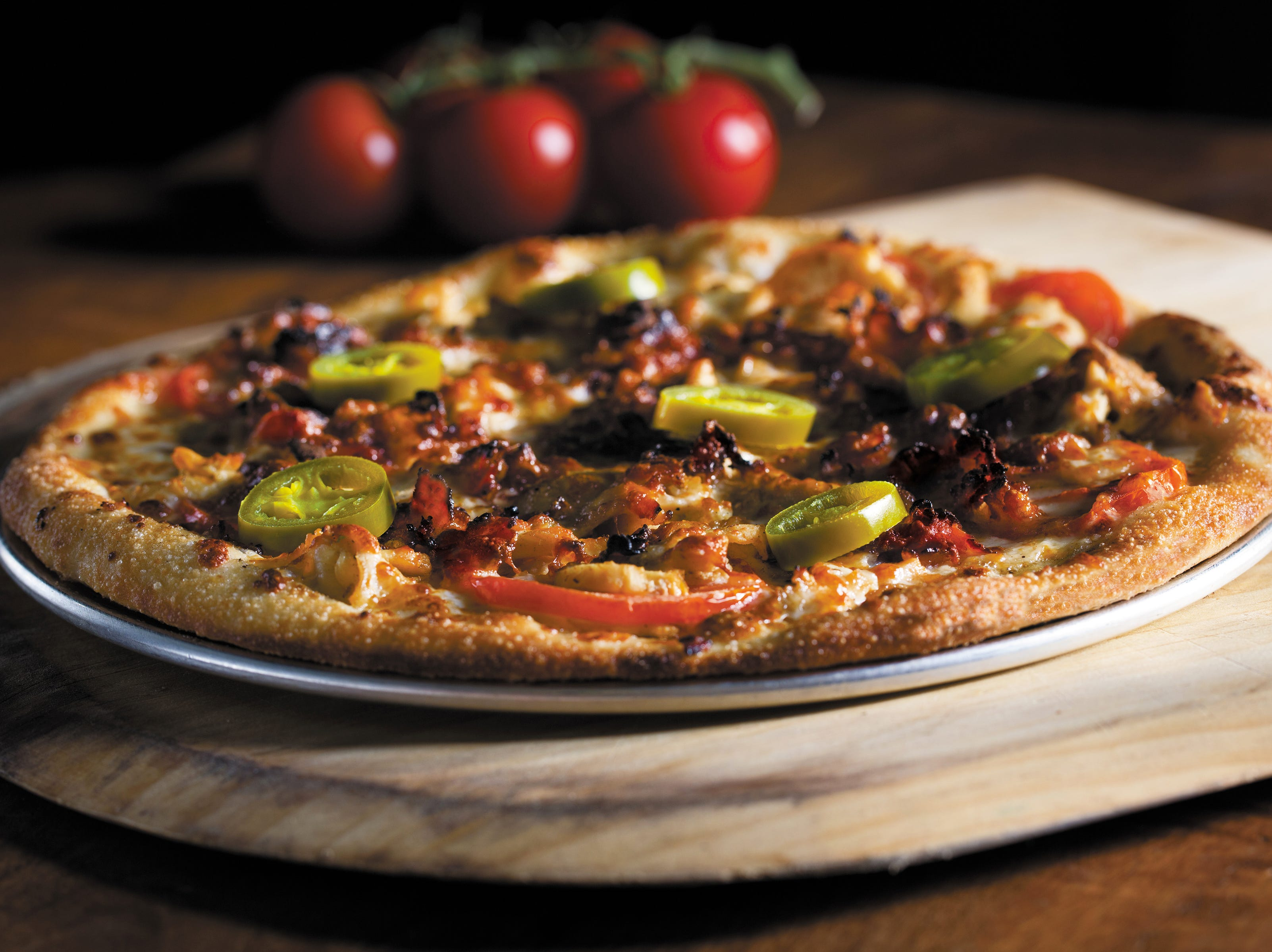 "Newk's ""Q"" Pizza, a Newcomb family recipe, features grilled chicken breast, a white barbecue sauce, crumbled bacon, vine-ripened tomatoes, house-shredded mozzrella and provolone cheeses on a crust brushed with chili oil and garnished with jalapenos."
