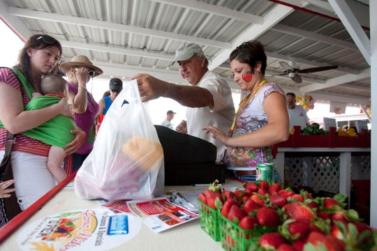 Mike Clevenger, owner of Farmer Mike's U-Pick, and Holly Nelson help patrons with their purchases during the first ever Farmer Mike's U-Pick Strawberry Festival in 2013.