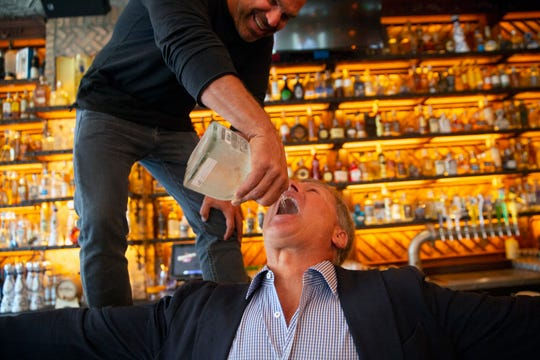 Rocco Mangel pours tequila in to Todd Herbst mouth during a soft opening of Rocco's Tacos & Tequila Bar, Tuesday, Feb. 26, 2019, in Naples.