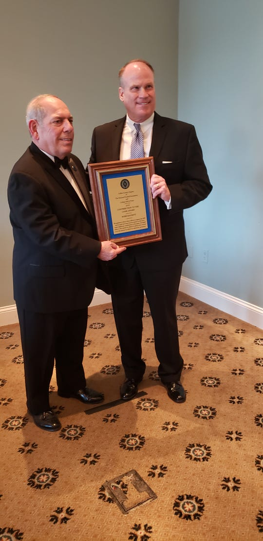 Robb Mackett (right) stands with National Football Foundation Collier County chapter president Matt Sellitto with the Contributions to the Game Award that Mackett received at the chapter's annual banquet on Monday.