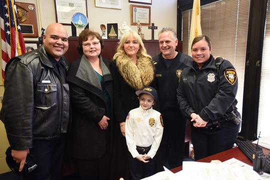 Delaney Kurdyla (age 8) of Wood-Ridge, cancer survivor and St. Joseph's Children's Hospital patient, has her picture taken with (L to R), Patrol Officer Eddy Pichardo, Grandmother Diane Kurdyla, Mother Kaitlin, Police Director Jerry Speziale and Officer Irsi Velez following her Swearing In ceremony as she experiences life as the Chief of Police for Paterson, photographed at Police Headquarters in Paterson on 02/26/19.