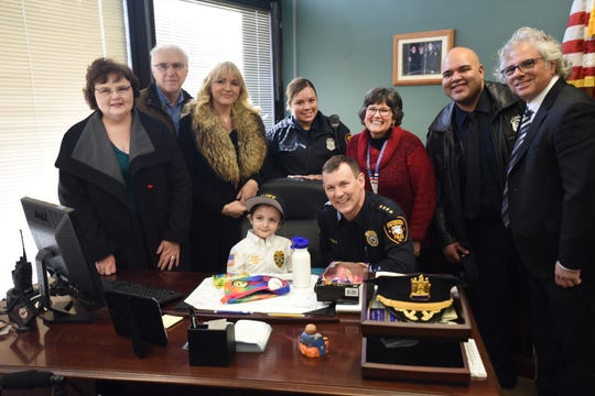 Delaney Kurdyla (age 8) of Wood-Ridge , cancer survivor and St. Joseph's Children's Hospital patient, has a group photo taken with Police Chief Troy Oswald and family members and officials from St. Joseph's Children's Hospita as she experiences life as the Chief of Police for Paterson, photographed at Police Headquarters in Paterson on 02/26/19.
