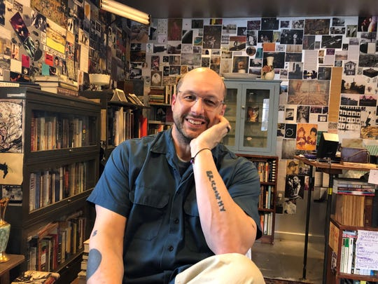 """Chris Napierala, executive director of the community music nonprofit Seed Artists, in his Montclair home office. His forearm tattoo spells out the name of jazz great Eric Dolphy, who """"completely  changed the way I listen to music."""" February 2019."""