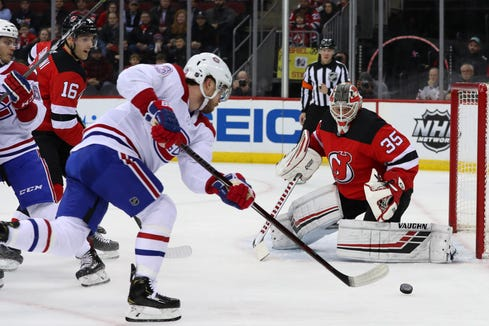 Montreal Canadiens center Max Domi (13) skates with the puck while New Jersey Devils goaltender Cory Schneider (35) defends his net during the first period at Prudential Center.