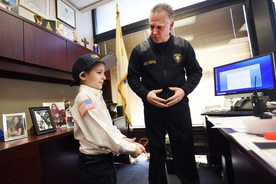 Delaney Kurdyla (age 8) of Wood-Ridge , cancer survivor and St. Joseph's Children's Hospital patient, talks with Police Director Jerry Speziale (R) prior to the Swearing In ceremony   as the Chief of Police for Paterson, photographed at Police Headquarters in Paterson on 02/26/19.