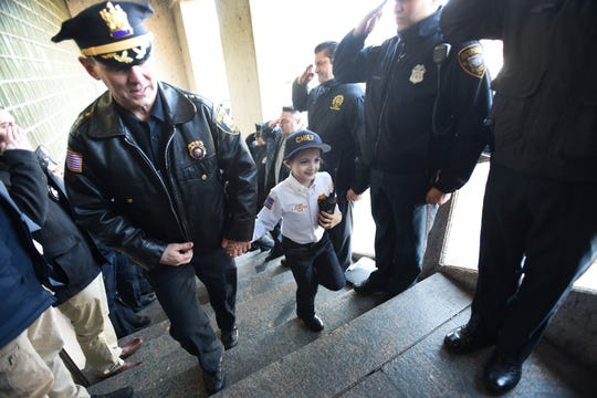 As she arrives, Delaney Kurdyla (age 8) of Wood-Ridge , cancer survivor and St. Joseph's Children's Hospital patient, walks up the stairs with Police Chief Troy Oswald as officers salute on each side of the stairs prior to the tour as the Chief of Police for Paterson, photographed  on 02/26/19.