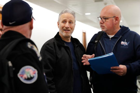 Entertainer and activist Jon Stewart, center, speaks with members of the FealGood Foundation as they arrive on Capitol Hill to speak with lawmakers about the compensation fund for victims of 9/11, Monday, Feb. 25, 2019, on Capitol Hill in Washington. Stewart has been involved in urging support for the first responders, volunteers, and survivors of the September 11 attacks. (AP Photo/Jacquelyn Martin)