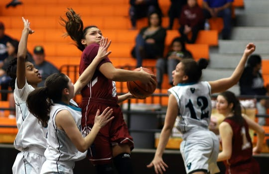 Freshman Lady 'Cat Harmanie Dominguez draws a crowd when she enters the paint. Dominguez dropped 13 points on the Knights.