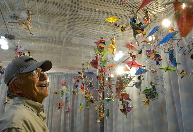 In this file photo, Stan Furber, of Las Cruces, smiles while looking at a collection of paper-mâché mobiles during the Las Cruces Arts Fair at the Las Cruces Convention Center. The mobiles were handmade by Sarena Mann.