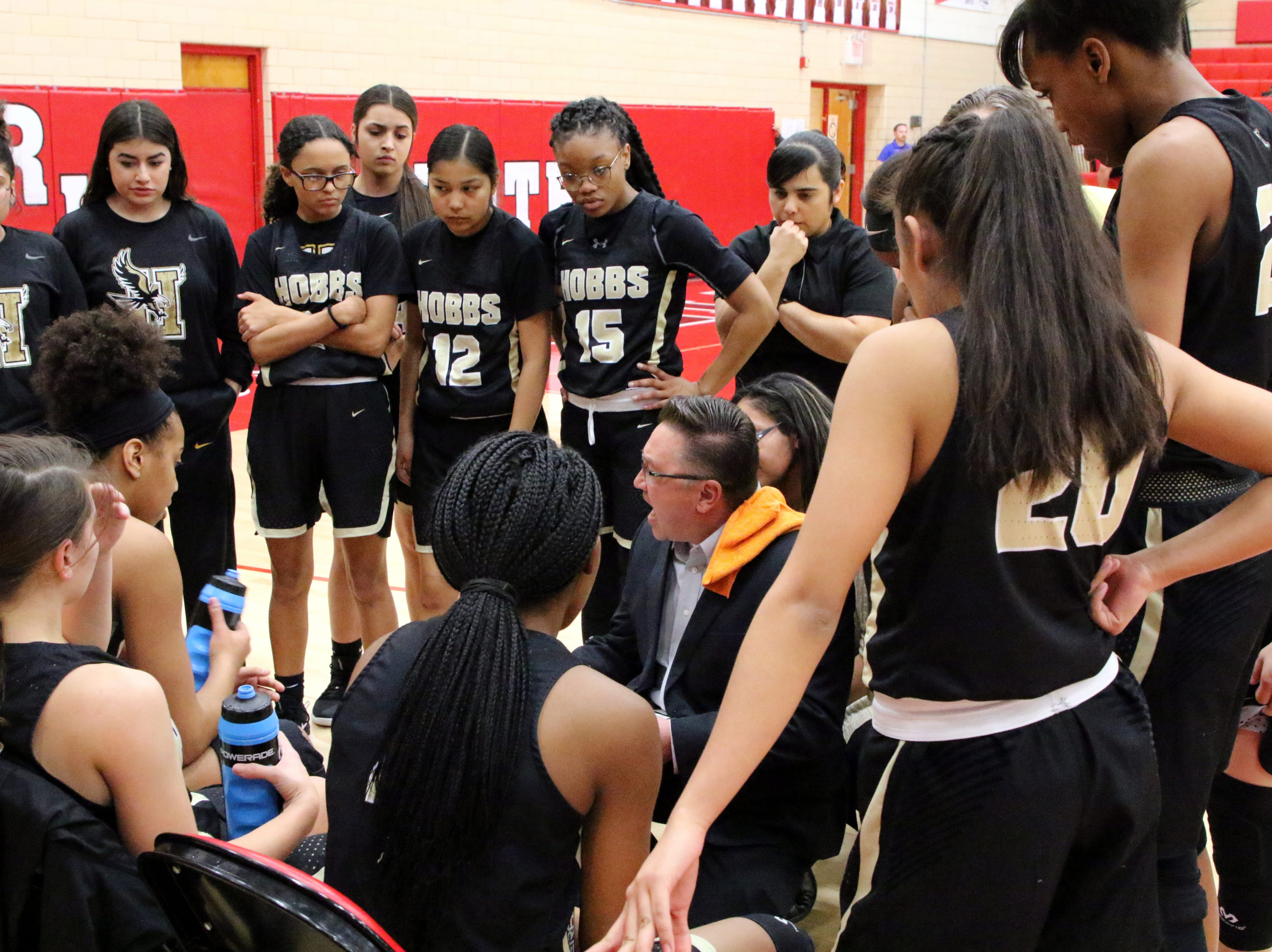 Hobbs coach Joe Carpenter talks to his team during a timeout on Monday.