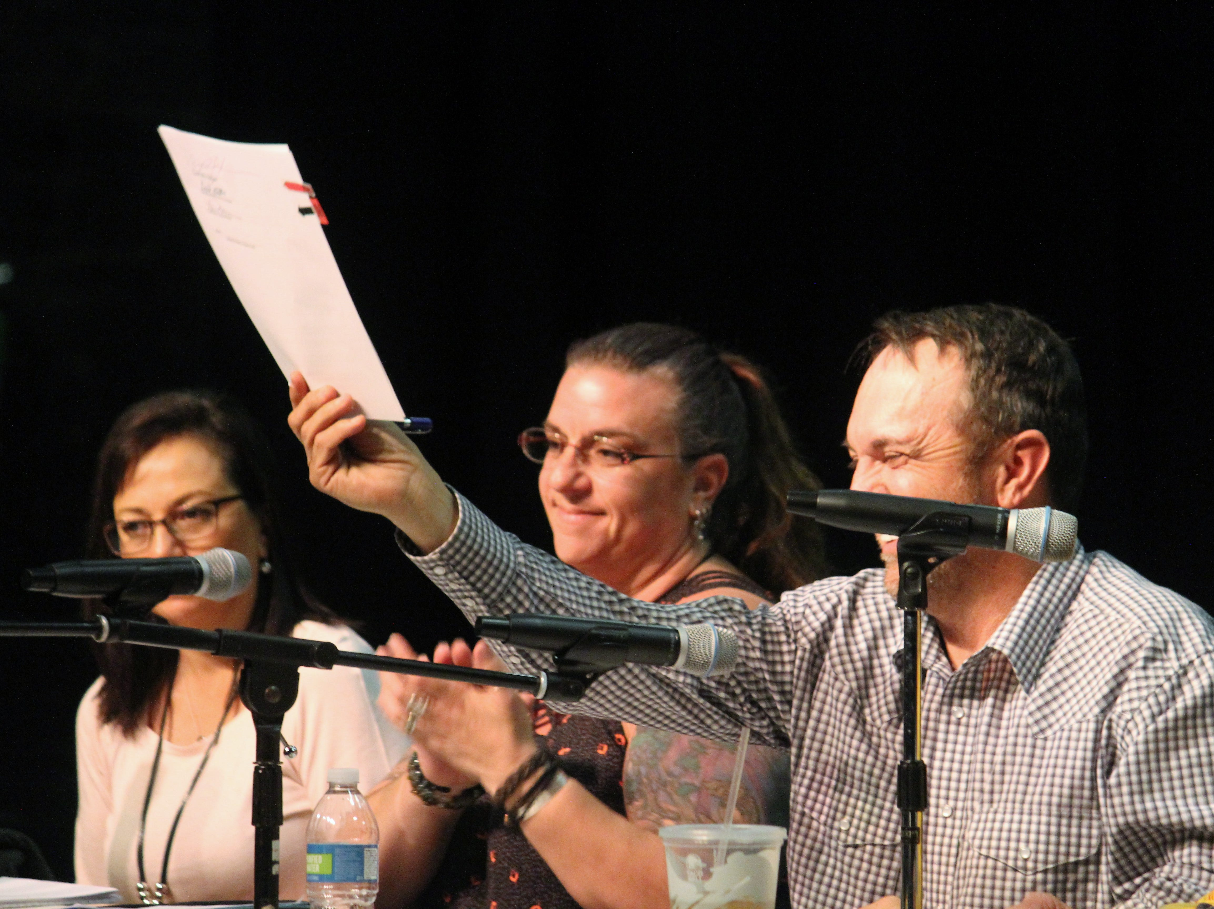 Couy Griffin hold up the resolution declaring Otero County a Second Amendment Sanctuary County at a special meeting Monday evening at the Flickinger Center for the Performing Arts.