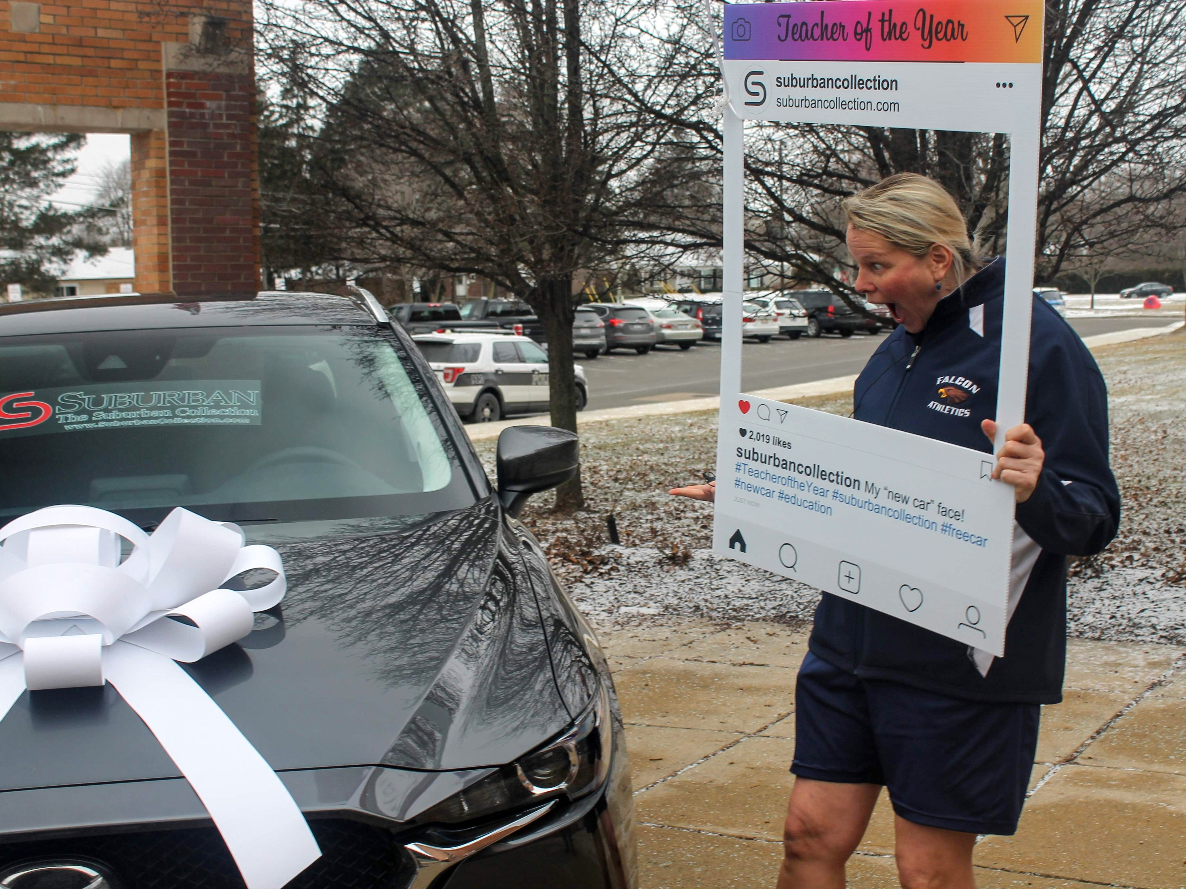 """Mary Sheltrown poses with her """"shocked"""" face while looking at a Mazda CX5 parked outside Farmington High School."""