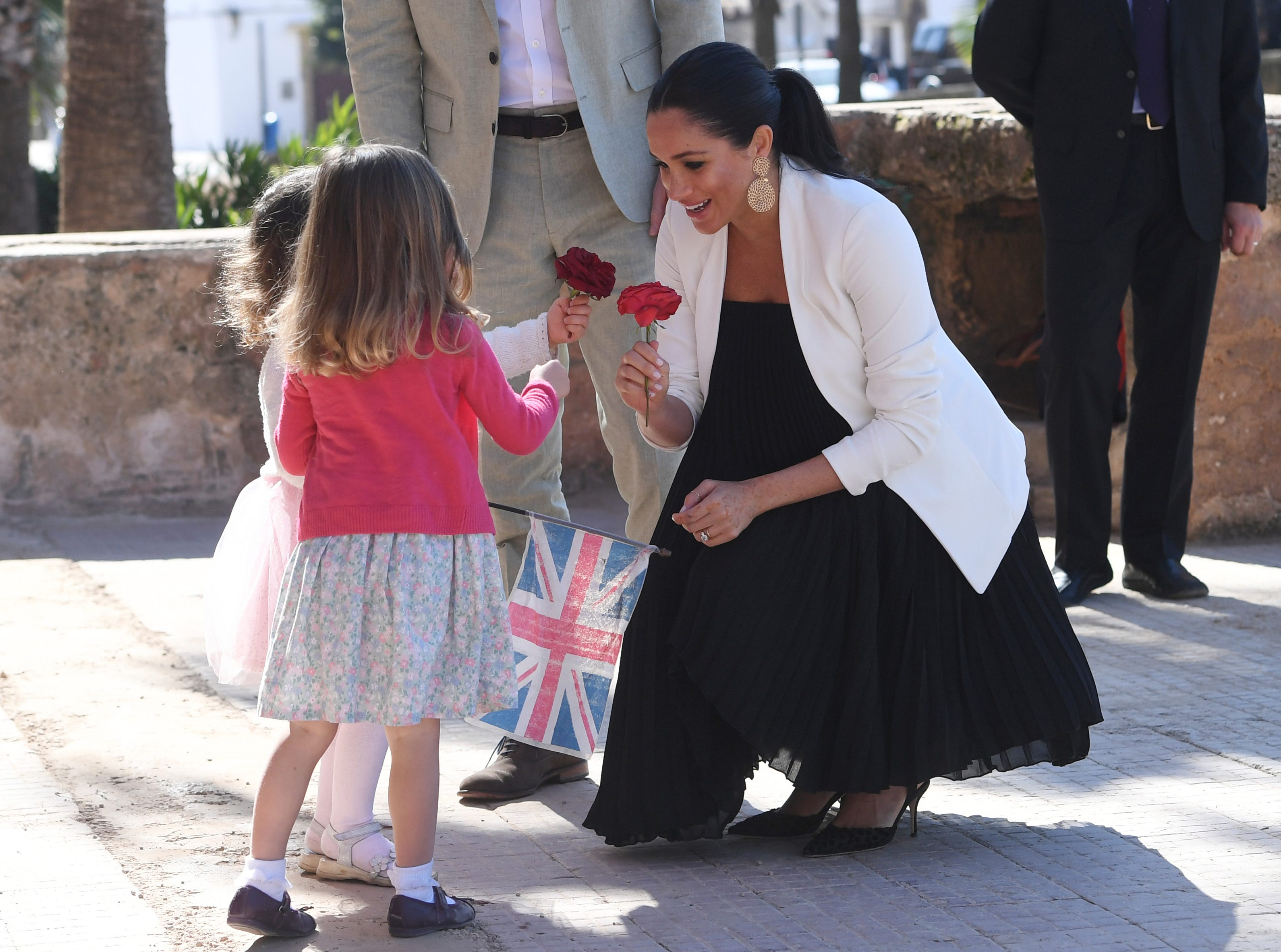 Britain's Prince Harry and Meghan, Duchess of Sussex speak with children as they visit the Andalusian Gardens in Rabat, Morocco, Monday, Feb. 25, 2019. The Duke and Duchess of Sussex are on a three day visit to the country.