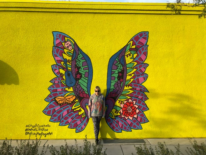 """Kelsey Montague with her mural """"What Lifts Your Wings - Coachella"""" in the city of Coachella."""