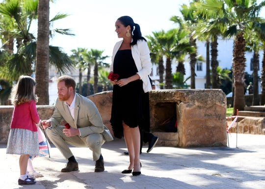 Britain's Prince Harry and Meghan, Duchess of Sussex speak to children as they visit the Andalusian Gardens in Rabat, Morocco, Monday, Feb. 25, 2019. The Duke and Duchess of Sussex are on a three day visit to the country.