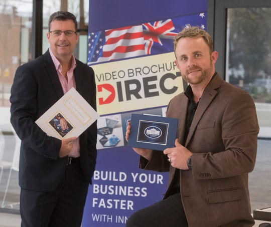 Brendan Farrugia and Aaron Ball, co-founders of  Video Brochure Direct, stand for a photo Tuesday with their video book.