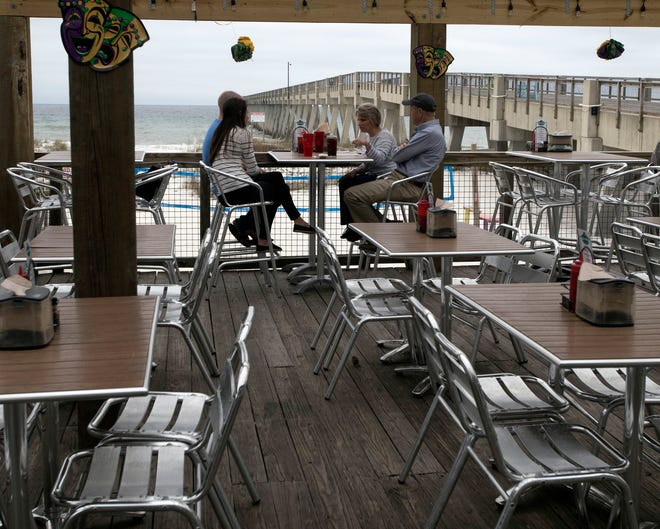 Visitors enjoy the mild weather with lunch at the Navarre Beach pier on Tuesday.