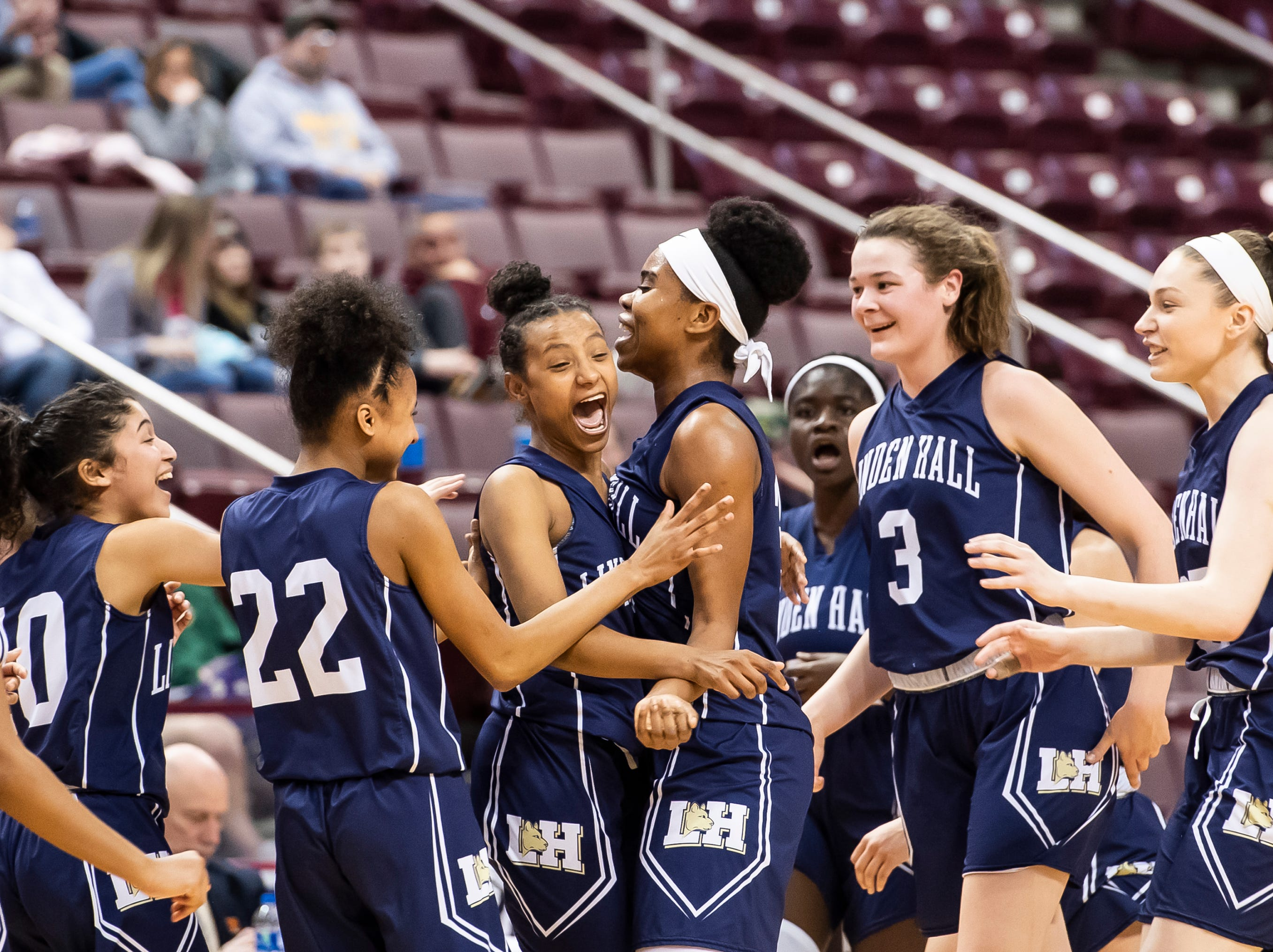Linden Hall players celebrate with Favour Mbeledeogu, center, after she scored a buzzer beater before halftime during the District 3 2-A girls championship game against York Catholic at the Giant Center in Hershey Tuesday, Feb. 26, 2019. The Fighting Irish fell 56-27.