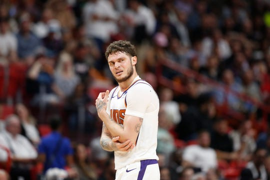 Phoenix Suns guard Tyler Johnson (16) holds his elbow after an injury during the second half of an NBA basketball game Monday, Feb. 25, 2019, in Miami, Fla. (AP Photo/Brynn Anderson)