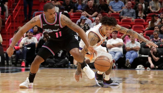 Miami Heat guard Dion Waiters (11) and Phoenix Suns forward Kelly Oubre Jr. (3) both dive for the ball during the second half of an NBA basketball game Monday, Feb. 25, 2019, in Miami, Fla. (AP Photo/Brynn Anderson)