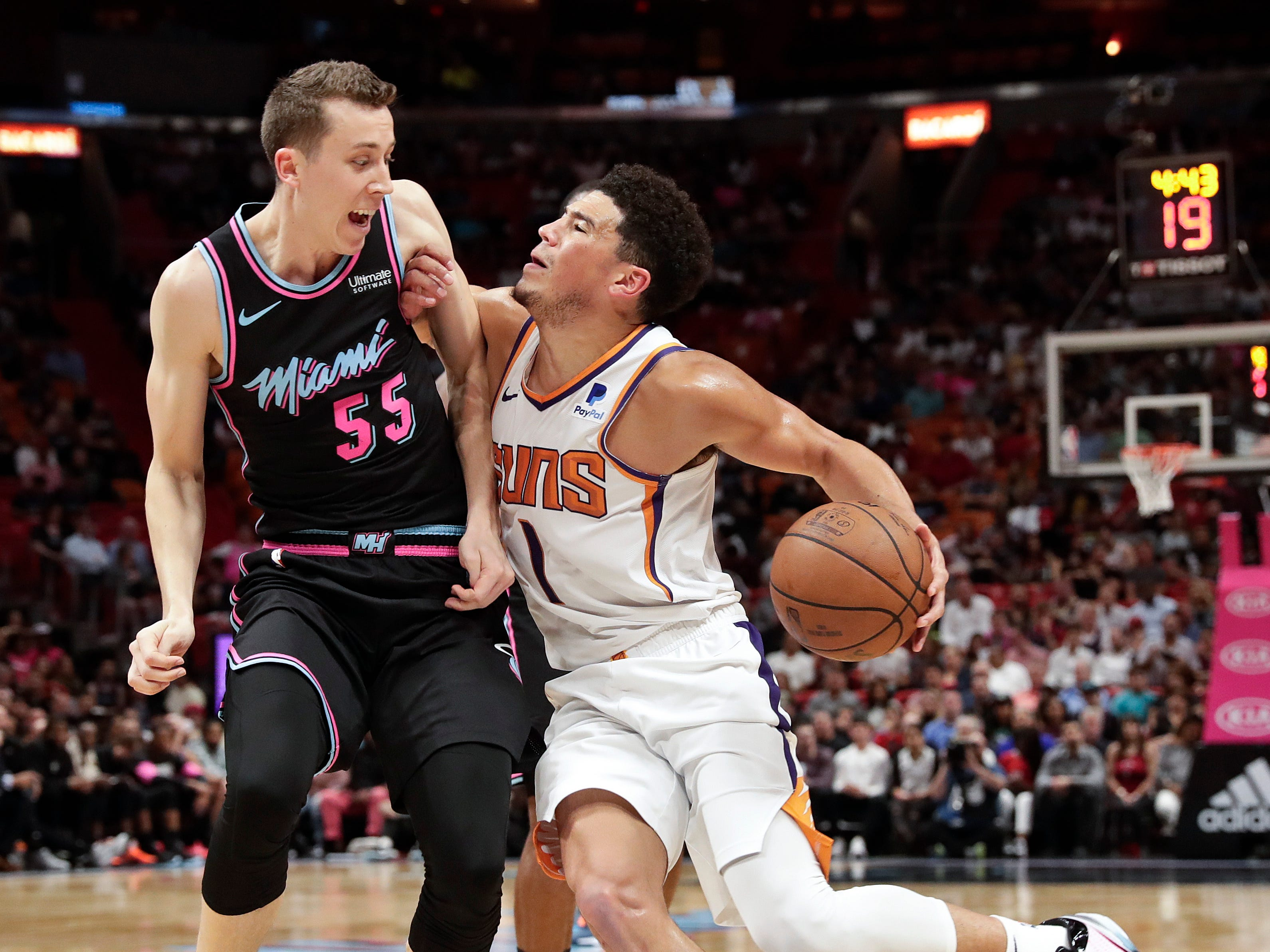 Miami Heat forward Duncan Robinson (55) fouls Phoenix Suns guard Devin Booker (1) during the first half of an NBA basketball game on Monday, Feb. 25, 2019, in Miami. (AP Photo/Brynn Anderson)