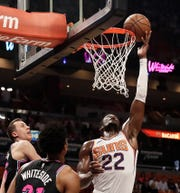Phoenix Suns center Deandre Ayton (22) shoots and scores against Miami Heat forward Duncan Robinson (55) and Miami Heat center Hassan Whiteside (21) during the first half of an NBA basketball game Monday, Feb. 25, 2019, in Miami. (AP Photo/Brynn Anderson)