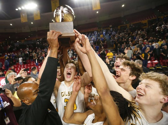 Gilbert players celebrate after winning the Boys State 5A Championship game against Millennium in Tempe, Ariz. Feb. 25, 2019.