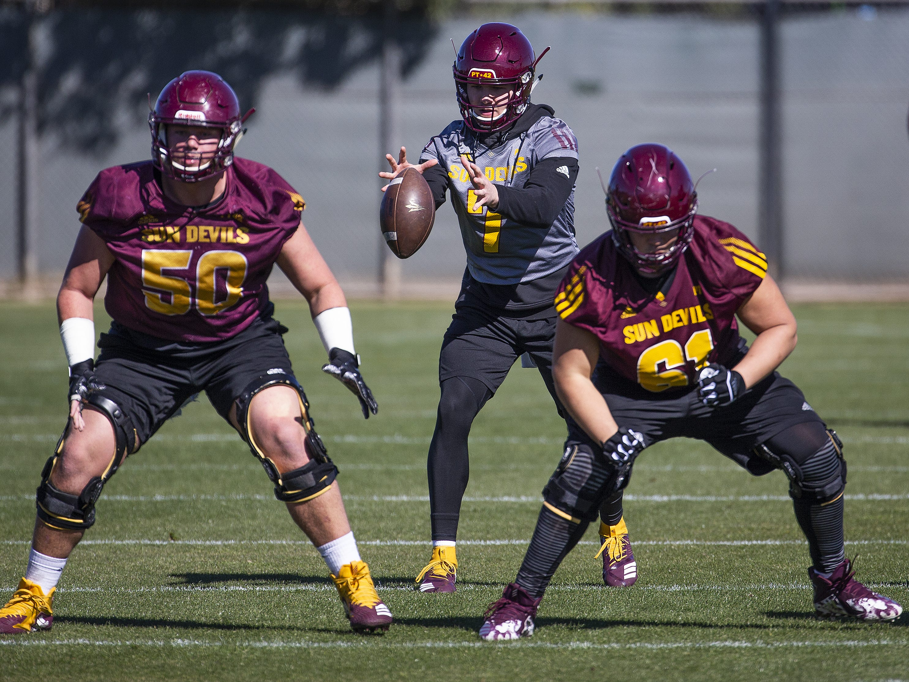 The Arizona State University football team practiced in Tempe, Tuesday, February 26, 2019.   Quarterback Ethan Long takes the snap as offensive linemen Jarrett Bell, left, and Dohnovan West, prepare to block.