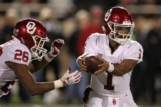 Oklahoma quarterback Kyler Murray (1) gets set to hand the ball off to running back Kennedy Brooks (26) during a game against Texas Tech.