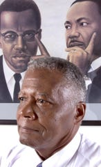 Former Chandler Mayor Coy Payne at home near a painting of Malcolm X and Martin Luther King Jr., whose holiday Payne advocated while on the Chandler City Council.