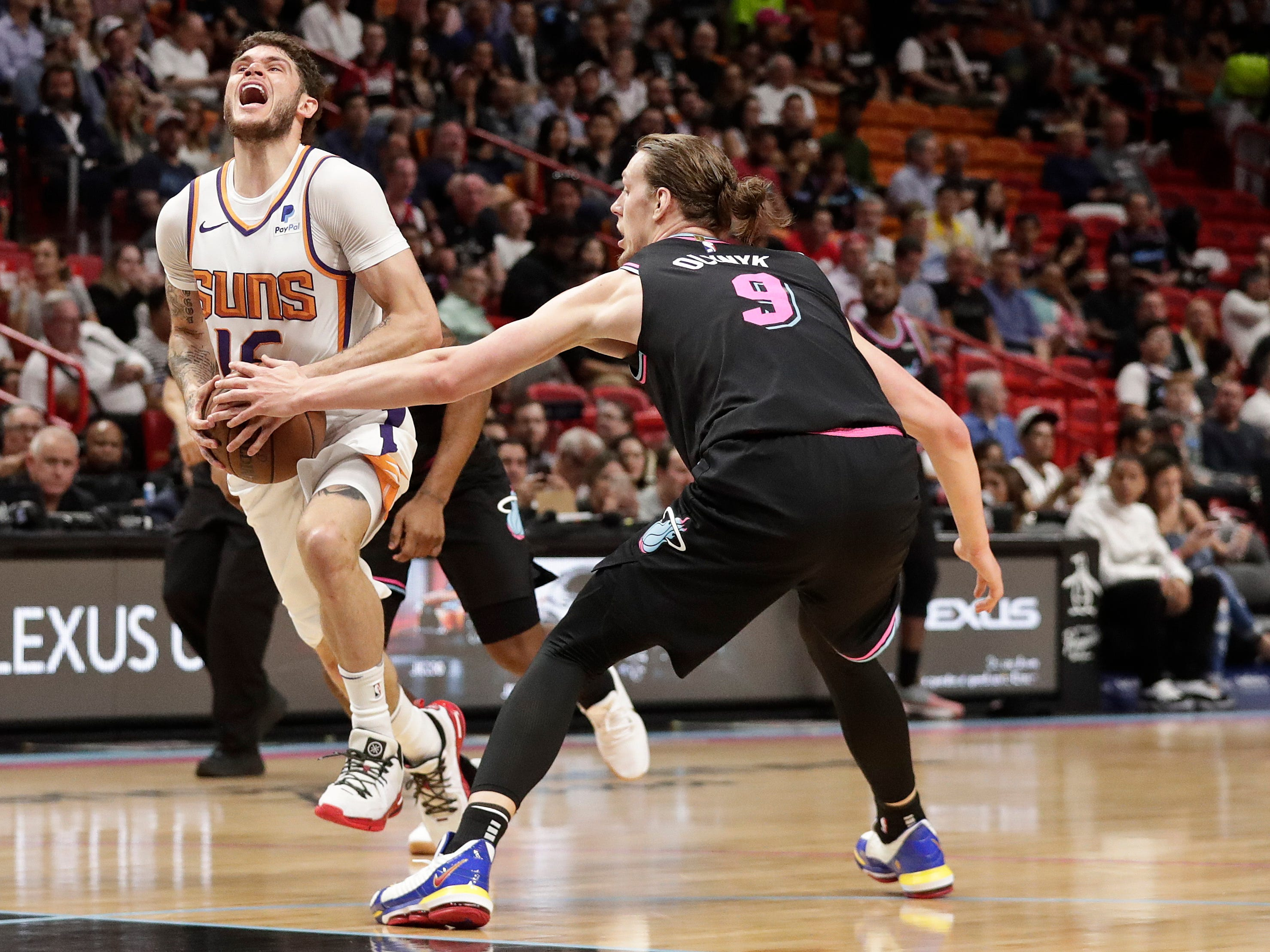 Phoenix Suns guard Tyler Johnson (16) reacts to a foul from Miami Heat forward Kelly Olynyk (9) during the first half of an NBA basketball game Monday, Feb. 25, 2019, in Miami. (AP Photo/Brynn Anderson)